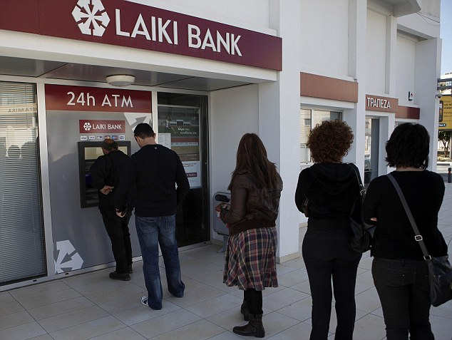 Panic: People queue withdraw their money from an ATM machine outside in Larnaca, Cyprus, after learning that the terms of a bailout deal includes a one-time levy on bank deposits