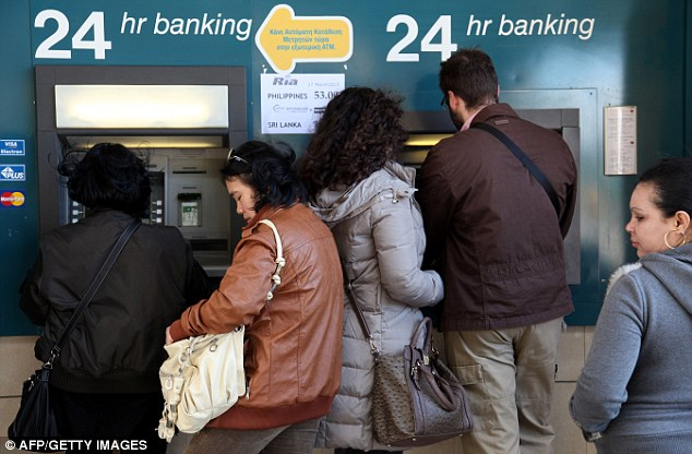 Queues: People withdraw money from a cash-point machine in the Cypriot capital of Nicosia today