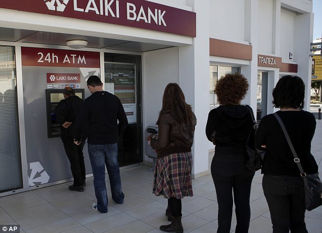 People queue to use an ATM machine outside of a Laiki Bank branch in Larnaca, Cyprus on Saturday