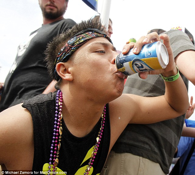 A college student chugs a beer in a crowd of Spring Break revelers at Coca Cola Beach on South Padre Island, Texas, where there were 1,000 DWI arrests during last year's spring break