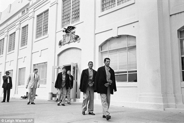 In this March 21, 1963 photo taken by Leigh Wiener and provided by the National Park Service, prison guard Jim Albright, (second from left), leads out the last prisoners from Alcatraz federal penitentiary