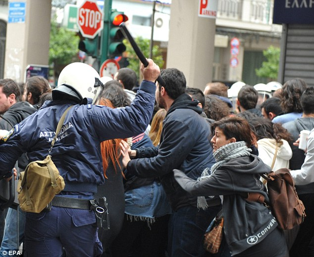 Clashes: A police officer is seen wielding a baton as he tries to control protestors who scuffled with officials during a parade to mark Greek Independence Day today