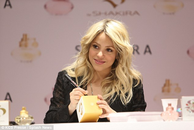 Gracious: Shakira signed perfume bottles for excited fans at the event