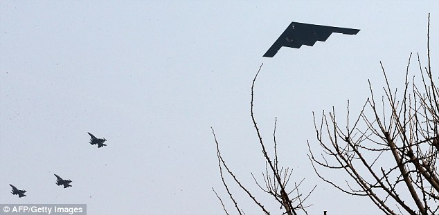 'Deterrence': A B-2 stealth bomber (right) soars through the sky over a U.S. air base in Pyeongtaek, South Korea, amid rising tension between the country and its neighbour the North