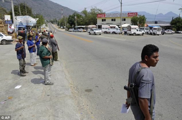 Checkpoints: The 'community police' have been stopping traffic on a main road to the capital Mexico City