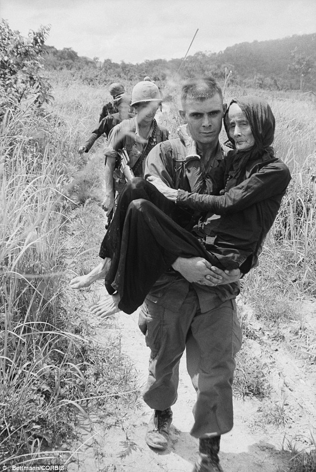 War: In this 03 Aug 1965 photo, an aged woman injured by a U.S.-Vietnamese air strike on a Buddist monastery 40 miles southeast of Saigon is carried to a hospital by airborne private Carl Champ of Furgitsville, West Virginia
