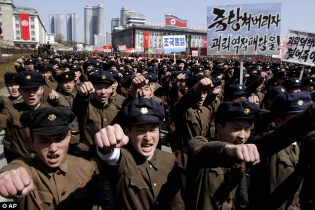 University students punch the air as they march through Kim Il Sung Square