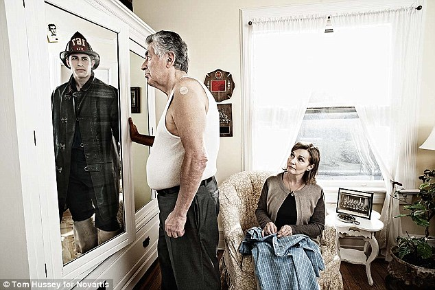Former lives: A retired fire fighter, who's actual photo is seen tucked in the mirror's top left corner, gazes into his reflection that shows a strapping young fire fighter staring straight back