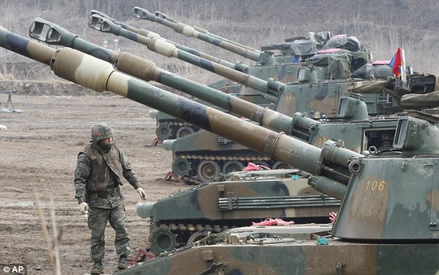 Preparing for war? A Marine from South Korea observes a line of K-55 howitzers during military drills