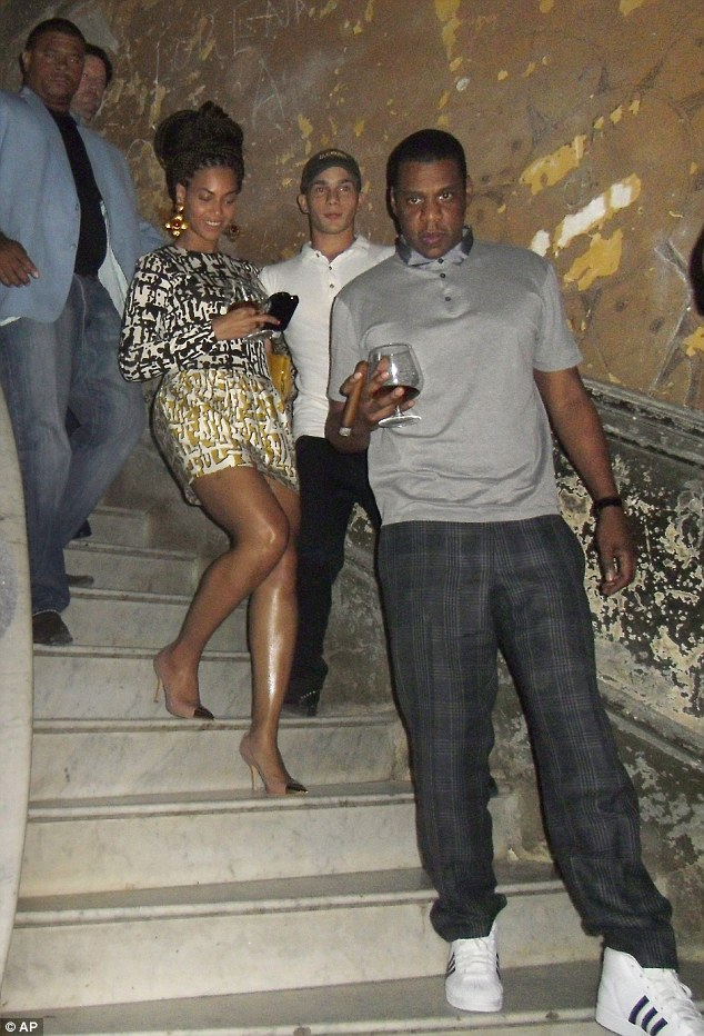 All eyes: Jay-Z appeared to stare protectively of his wife who carefully stepped behind him in heels as they walked into the flash of waiting cameras
