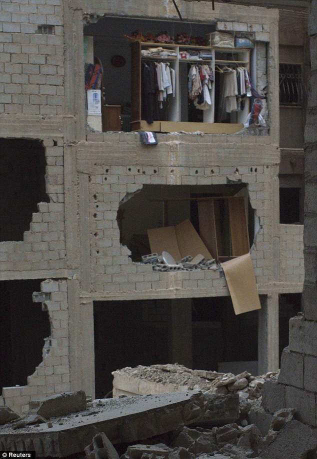 Bombed out: Clothes are seen hanging in a closet in a damaged apartment building