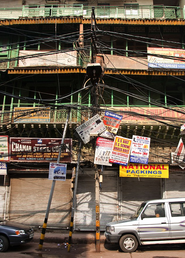 Cable junction: The electricity wires dominate the landscape as a car passes underneath in Old Delhi