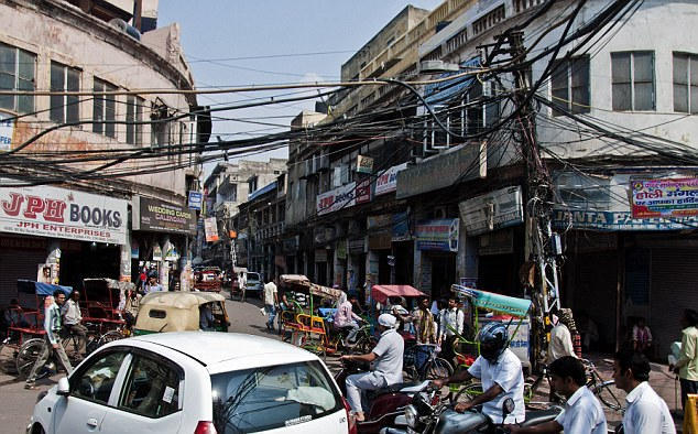 Cable spaghetti: The twisted lines of electricity wires cross a busy street in Old Delhi but the locals pay no attention to the danger above them