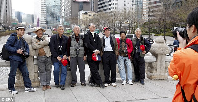 Leave, now: Foreign tourists pose for a picture in Seoul. North Korea urged foreigners in South Korea to evacuate