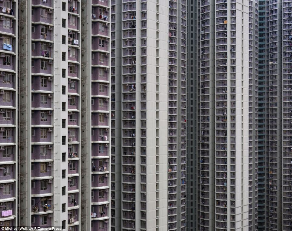 Shoulder to shoulder: The thousands of residents of these Hong Kong apartment buildings go about their daily lives in extremely close proximity to their neighbours