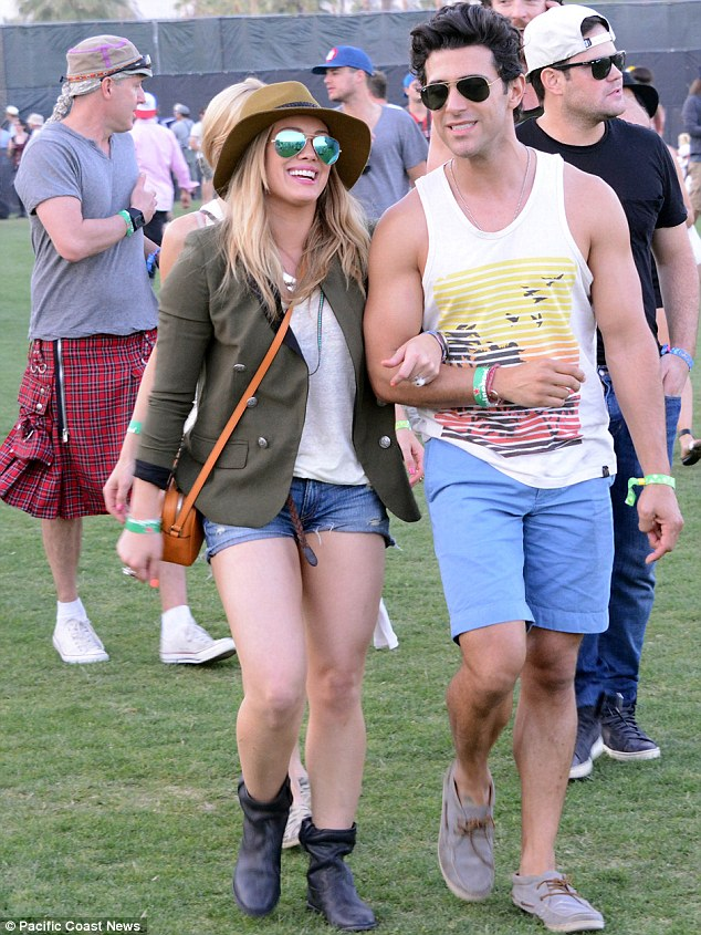 Adult time: Actress Hilary Duff looked free and easy as she strolled through the Coachella Music Festival Friday with an unidentified friend. Her husband, Mike Comrie, far right, also attended the Indio, California annual fete.