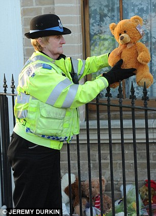 Remembrance: A police community support officer joined those laying tributes to the children