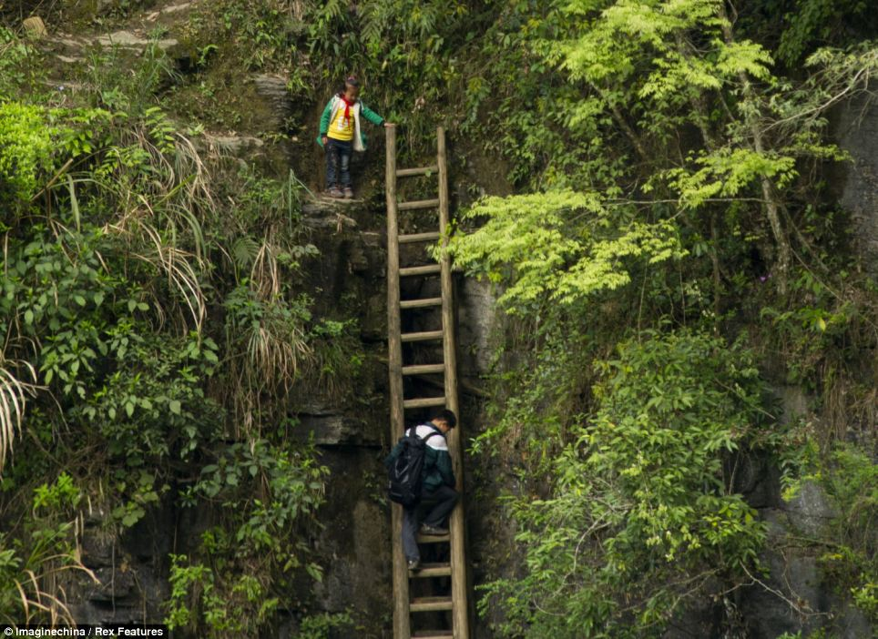 A schoolgirl holds the ladder for others to come up safely behind her