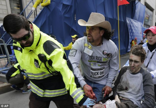 Suffering: A man who appears in severe pain is rushed away from the scene for aid