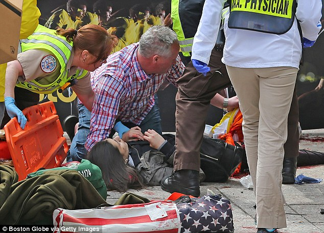 Aid: Emergency personnel respond to an injured woman after two explosions went off today