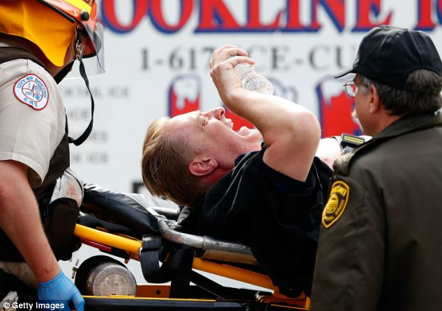 Suffering: A man is loaded into an ambulance after he was injured by one of two bombs at the finish line