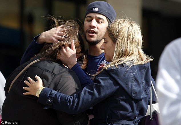 Overwhelmed: People comfort each other after the explosions, which killed two people on Monday