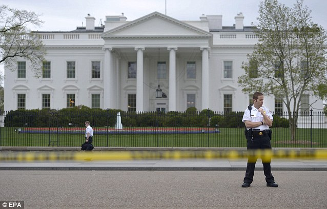 Uniformed Secret Service officer stands guard in front of the White House as the surrounding area have been closed