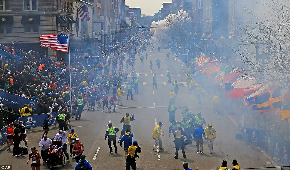 Exact Moment: People react as an explosion goes off near the finish at the Boston Marathon finish line on Monday, sending authorities out on the course to carry off the injured