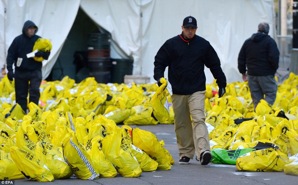 Sorting through: Bags of people's belongings are sorted near to the Boston Marathon finish line on Tuesday as investigations continue into the bombings