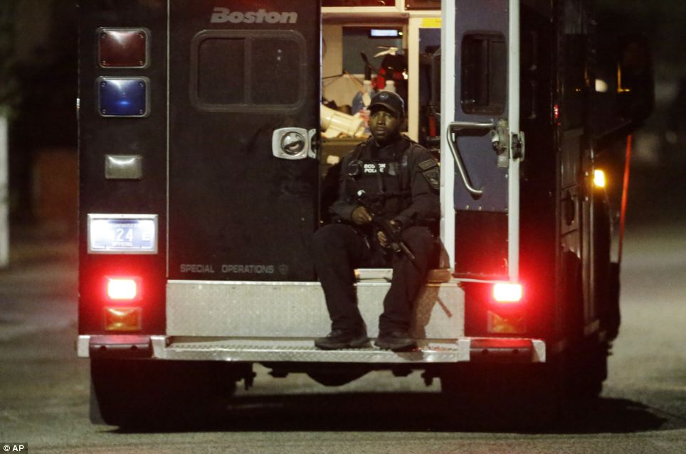 Alert: A police officers rides in the back of a van with his weapons out following a tense night of police activity