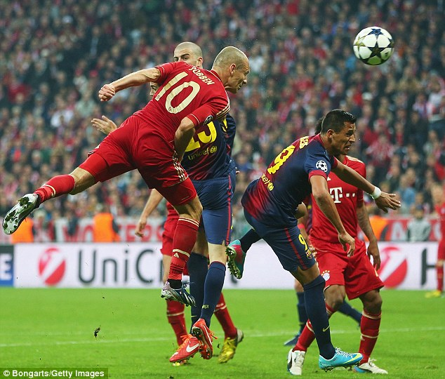 Leaping: Robben jumps to win a header against falling Barcelona attacker Alexis Sanchez (right)