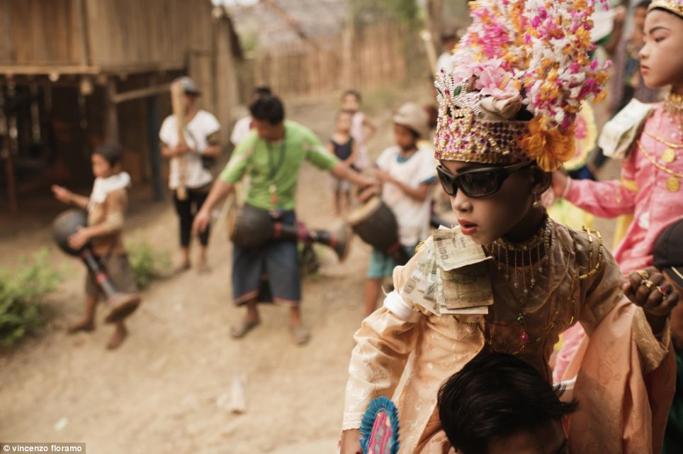 At the Mae La refugee camp, during Ta Pwe celebrations, children are carried on their parents' shoulders around the streets. In this photo Saw Win Gy is pictured on his uncle's shoulders