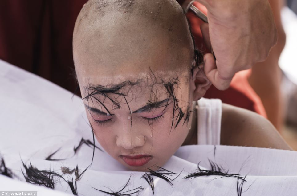 Saw Win Gy has his head shaved by a monk at the Thirisanda Buddhist Monastery at Mae La refugee camp