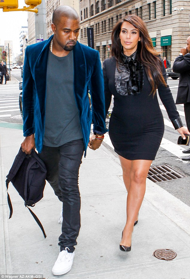 Figure-hugging: Kim also wore a black dress for the outing which clung to her baby bump