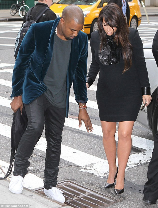 Careful: Kanye showed his protective side again on Tuesday when he steered his heavily pregnant girlfriend away from a storm drain