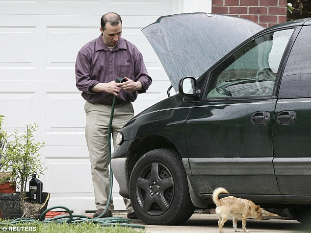 Monitored: Everett Dutschke, working on his mini-van in his driveway in Tupelo Mississippi on April 26, had been under surveillance this week, police said