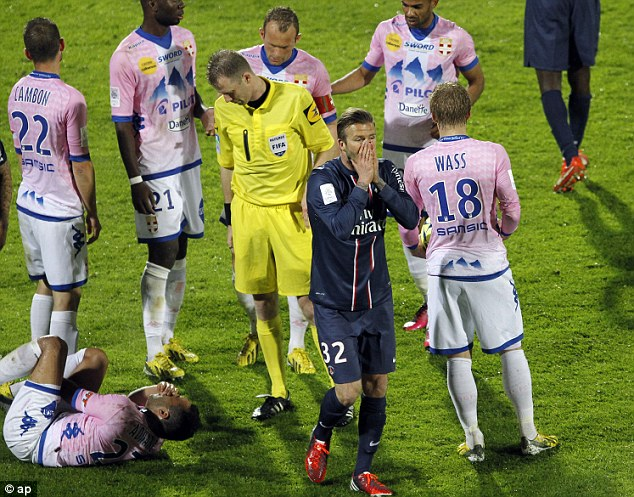 Sour end: Beckham makes his way off the pitch as Adnane lays on the floor