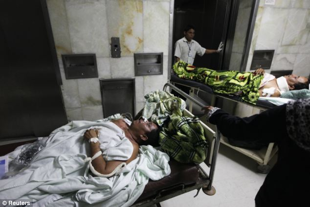 Human misery: Two men on stretchers are taken to the operation room at a local hospital after they had been attacked by a gang in San Pedro Sula