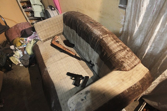 Deadly: Confiscated weapons lie on a couch after the arrest of several members of the Mara 18 street gang after a shoot-out with police and military during an anti-drug operation in San Pedro Sula last month