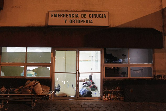 Overrun: Family members of patients sleep in a corridor of the emergency ward. Arms trafficking has flooded the country with nearly 70 per cent illegal firearms