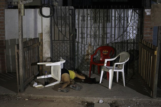 Gunned down: The dead body of a woman who was shot dead by two gunmen on a motorcycle is seen at a crime scene in San Pedro Sula