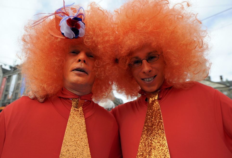 Proud: Two men wearing orange, the royal colour. The Netherlands is celebrating Queen's Day which also marks the abdication of Queen Beatrix