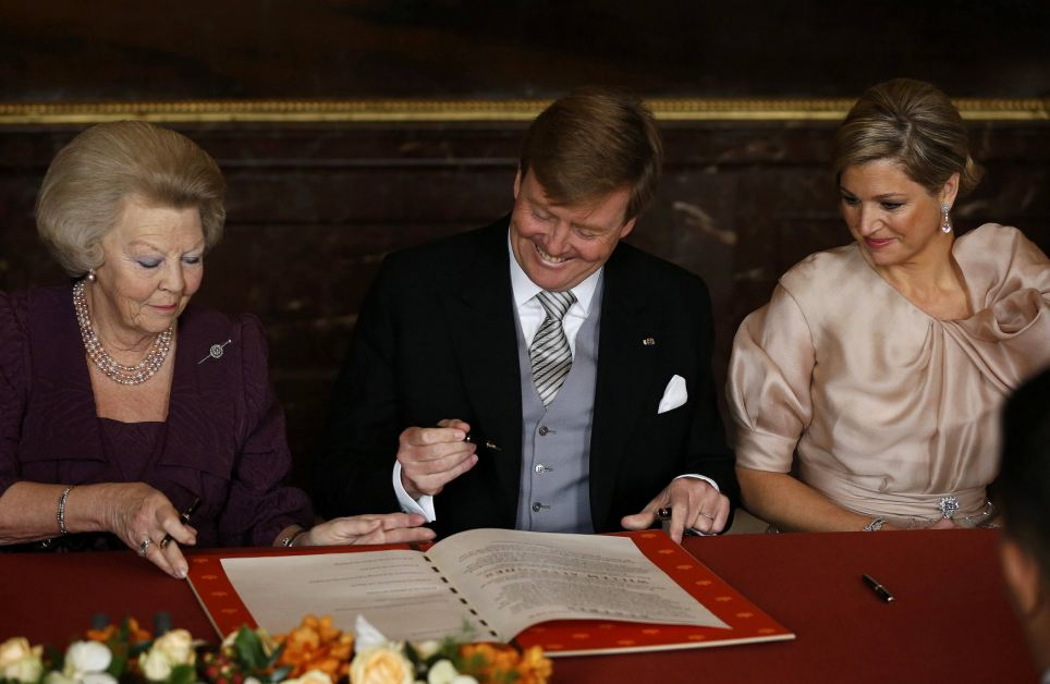 New generation: Queen Beatrix passes the act of abdication to her son Crown Prince Willem-Alexander who smiled widely as he signed the act