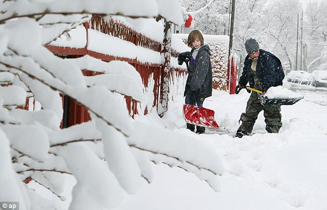 Shovels at the ready: Kyle MccLelland, left, and Matthew Cannon, right, shovel snow outside Cannon's house in Cheyenne, Wyoming. Cheyenne received more than a foot of snow