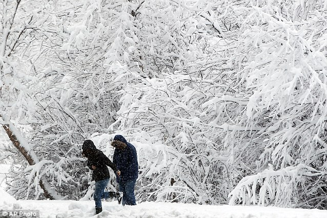 Not your typical spring day: Emily Jeffer, left, and Marge Jeffers try to navigate snow in Lions Park in Cheyenne, Wyoming after more than a foot of snow fell