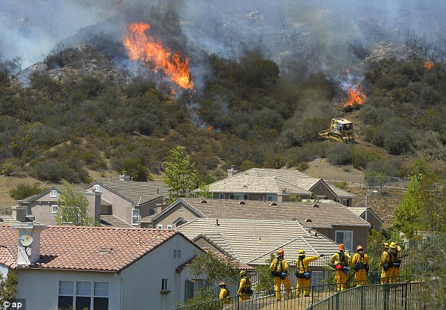 Evacuation: Firefighters stand and watch as bulldozers clear a firebreak near a wildfire burning along a hillside near homes in Thousand Oaks, California