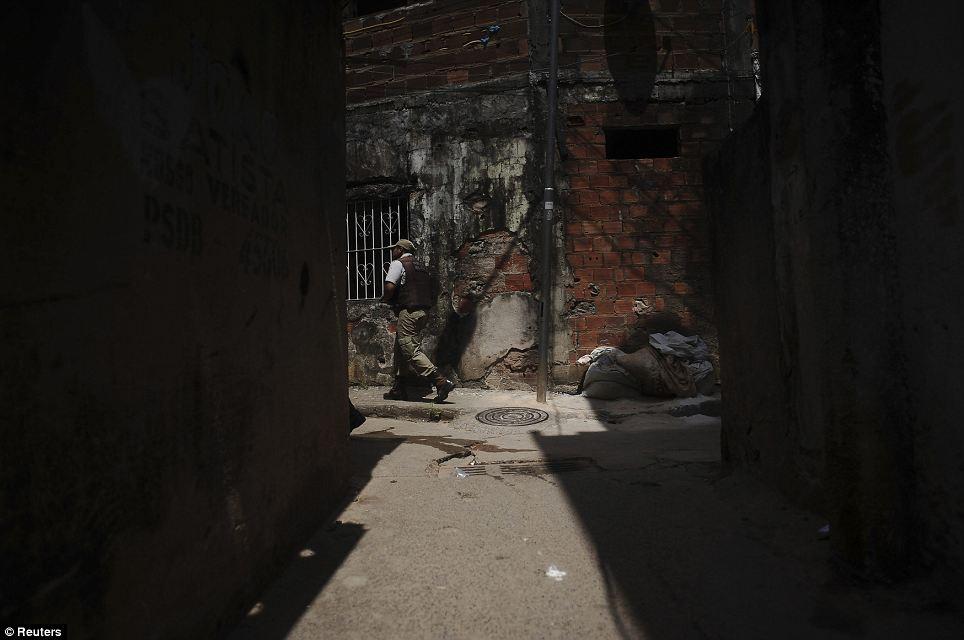 Behind enemy lines: Police officers patrol the narrow, winding alleys of the Nordeste de Amaralina slum complex in Salvador