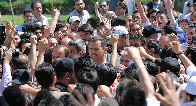 Surrounded: President Assad walks in the centre of a crowd in Damascus after unveiling a statue dedicated to students who have died in the fighting
