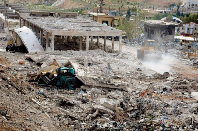 Aftermath: Bulldozers work to remove rubble after the Israeli airstrike in the Al-Hama area near Damascus