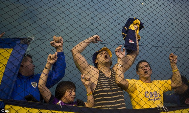 Loyal: Boca fans cheer on the home team as flares go off in the background